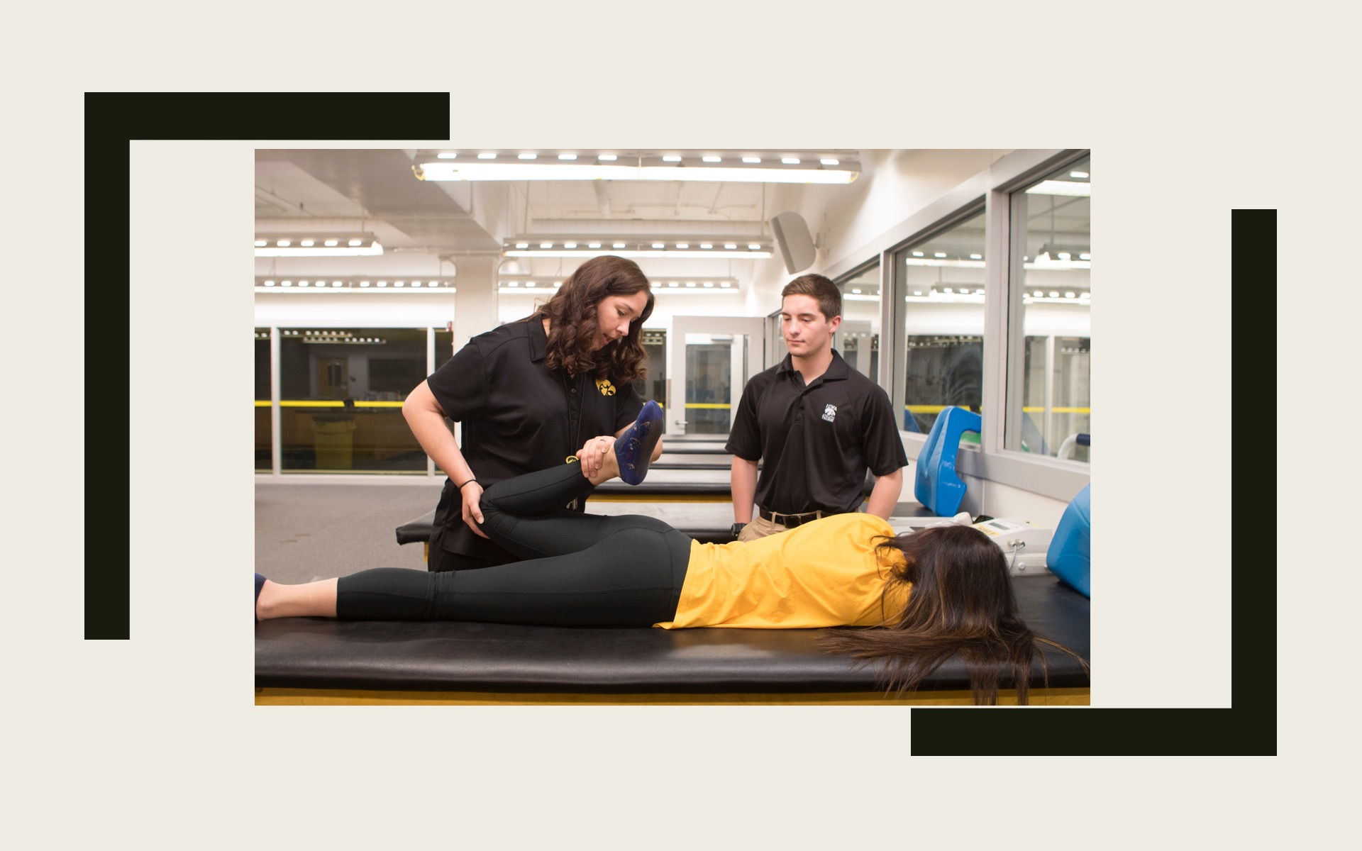 Faculty demonstrating a supine quadricep stretch to a student